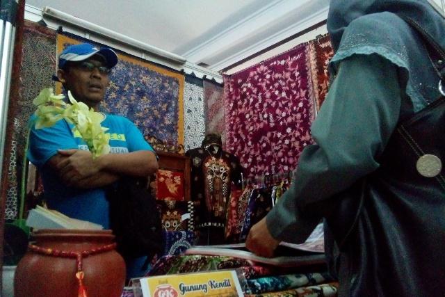 """Hawin Wilopo, pemilik gerai penjualan batik """"Gunung Kendil"""" melayani salah seorang pembeli di stan pamerannya di Rembang Expo 2015 di Balai Kartini, Rabu (27/5/2015). (Foto: Pujianto)"""