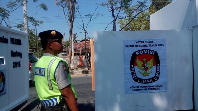 Seorang anggota polisi dari Polres Rembang melihat replika kotak suara pada acara kirab kampanye damai Pilkada Rembang, 29 Agustus 2015. (Foto: Pujianto)