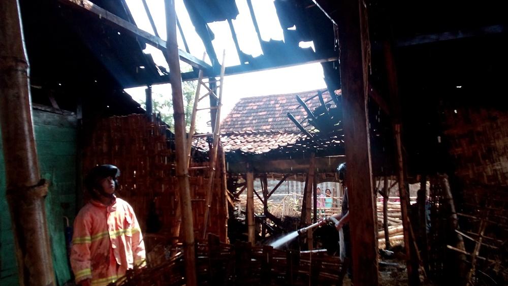 Petugas pemadam kebakaran masih menyemprotkan air, meski api sudah padam, guna memastikan tidak adanya lagi sisa titik api, pada sebuah kasus kebakaran di Desa Megulung Kecamatan Sumber, Sabtu (21/11/2015) pagi sekitar pukul 08.00 WIB. (Foto: Pujianto)