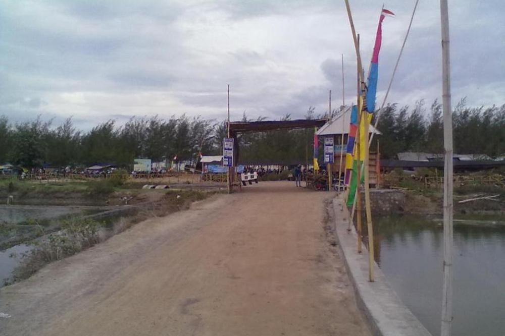 Kondisi akses jalan menuju Pantai Karangjahe sekilas tampak mulus ketika cuaca kering, namun berubah menjadi becek dan terkesan kumuh ketika turun hujan. (Foto: Mukhammad Fadlil)