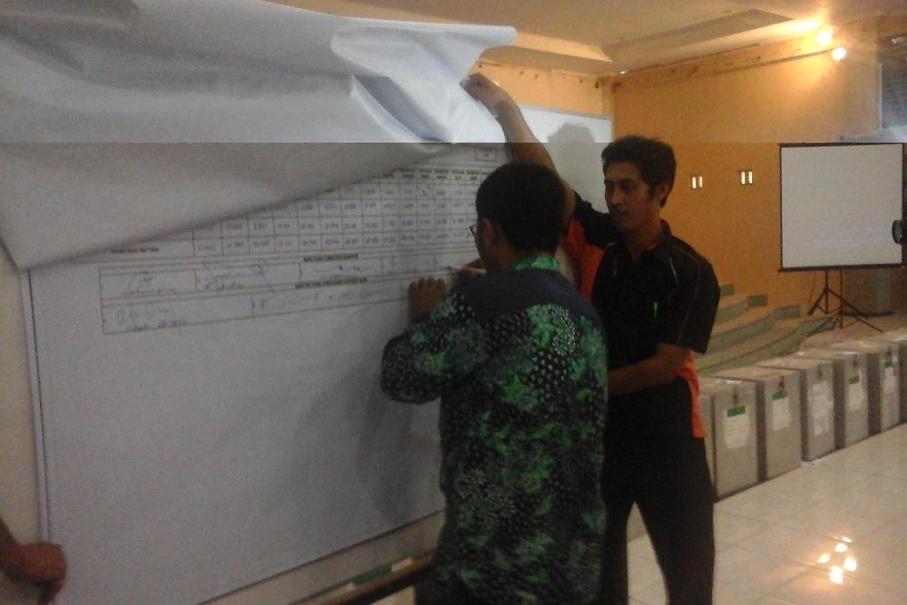 Komisioner KPU Rembang HM Adib Ulinnuha membubuhkan tanda tangannya pada plano rekapitulasi hasil penghitungan perolehan suara di tingkat kabupaten pada Pilbup Rembang 2015 di Hotel Puri Indah, Rabu (16/12/2015) siang. (Foto: Pujianto)
