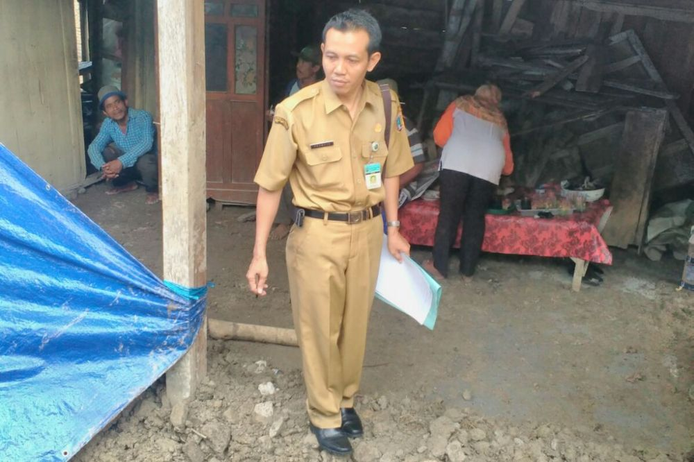 Kepala Seksi Tanggap Darurat BPBD Rembang Pramujo saat melakukan pendataan terhadap dampak longsor yang menimpa bangunan rumah milik Jalil, warga Desa Kumbo Kecamatan Sedan, Senin (7/12/2015). (Foto: Pujianto)
