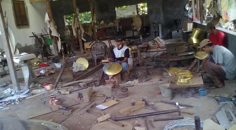 Perajin kuningan di Desa Jolotundo Kecamatan Lasem sedang sibuk mengerjakan order kerajinan di bengkel kerja mereka, Kamis (24/12/2015) pagi. (Foto: Mukhammad Fadlil)