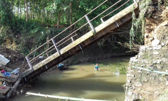Salah seorang warga membersihkan hambatan di aliran sungai di bawah Jembatan Tegalgeneng yang ambruk pada Sabtu 18 Juni lalu. Sampai dengan Selasa (21/6/2016), jembatan darurat belum dibuat, tetapi ditargetkan beres pada Sabtu 25 Juni mendatang. (Foto: Pujianto)
