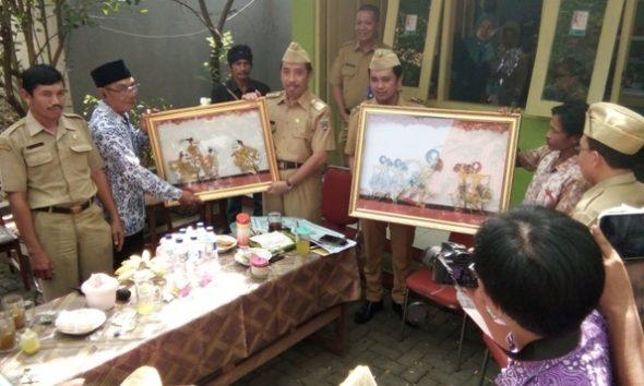 Bupati Rembang Abdul Hafidz (kiri) dan Wakil Bupati Rembang Bayu Andriyanto menerima  seserahan wayang gagrak pesisiran dari dalang dan pihak Pemerintah Desa Sendangasri Kecamatan Lasem di penghujung jumpa pers pada Senin (5/9/2016) kemarin. (Foto: Pujianto)