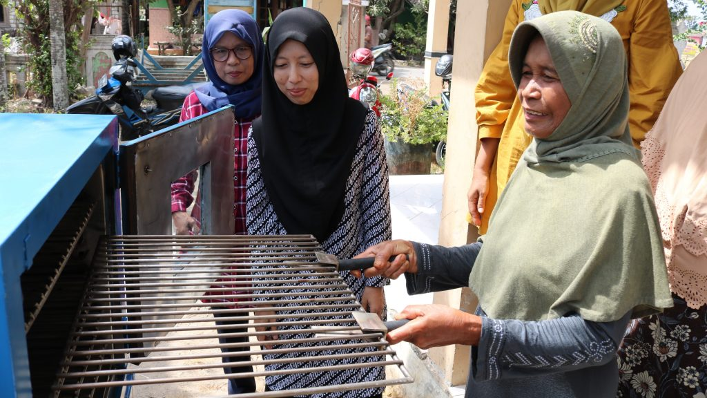 Ketua Pelaksana Program, Rikah sedang mengajari warga Desa Pasarbanggi Kecamatan Rembang cara menggunakan mesin pengasapan ikan, baeberapa waktu lalu. (Foto: mataairradio.com)